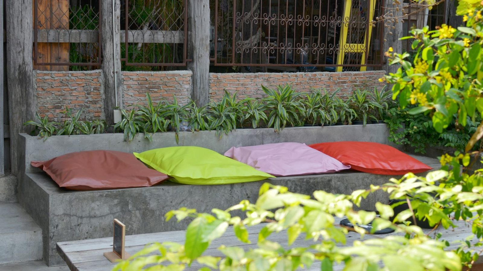 stone bench in a garden with various coloured cushions