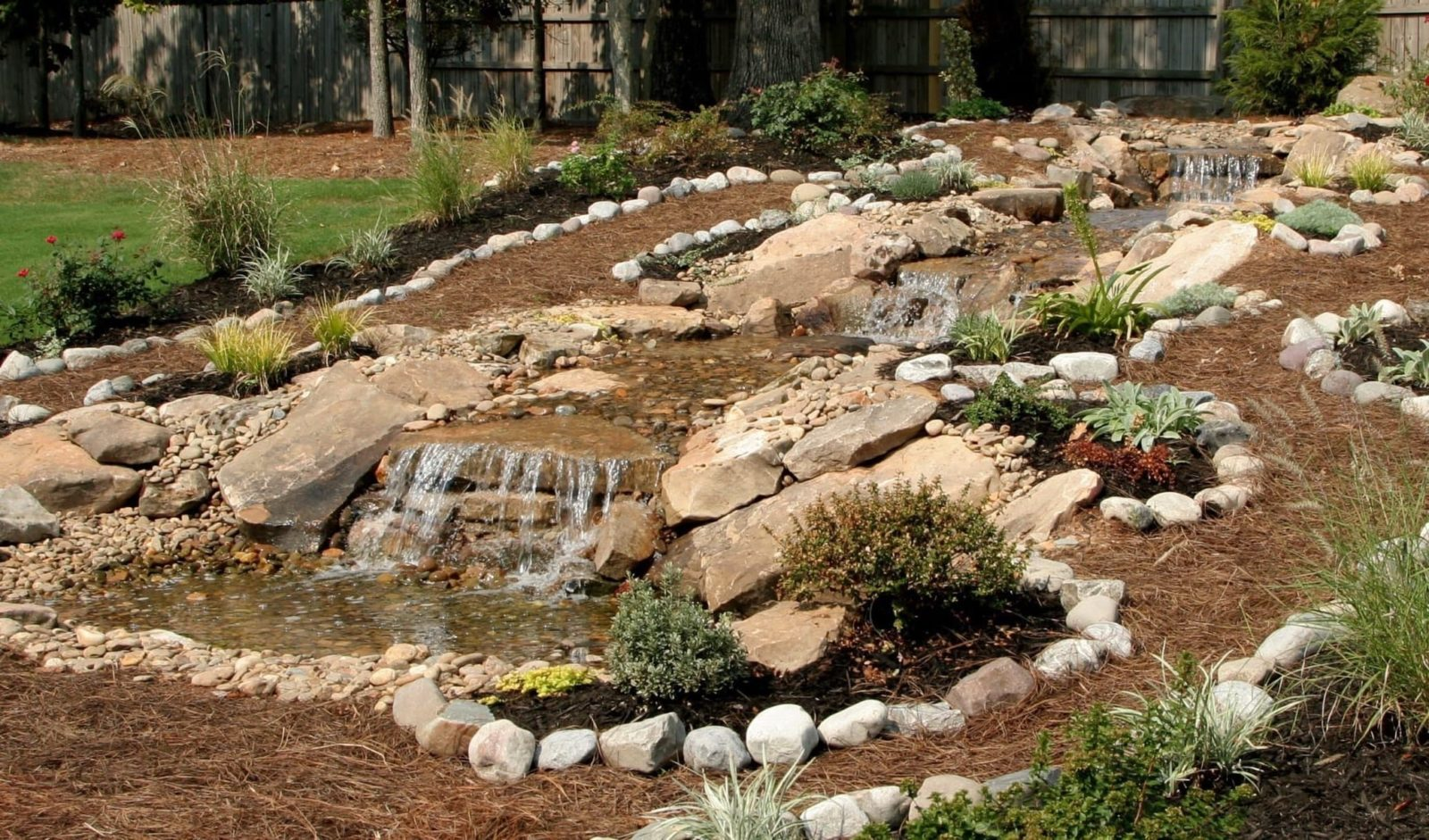 landscaped garden slope with rocks and waterfall