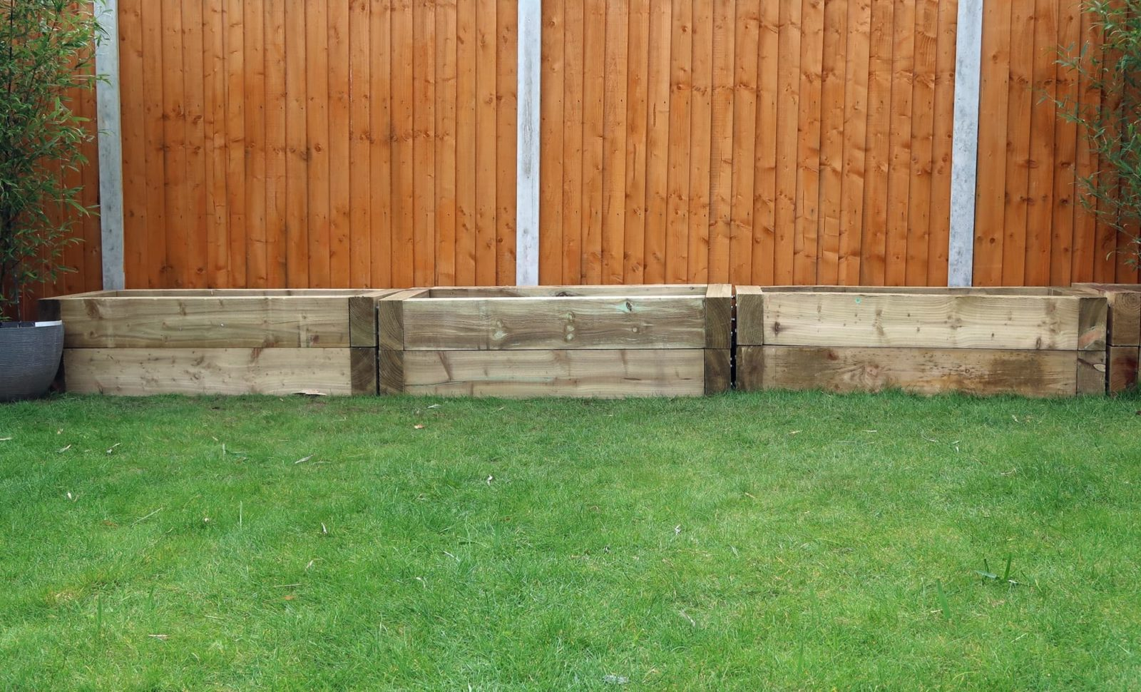 raised wooden trough planters with a lawn in the foreground and fence in the background