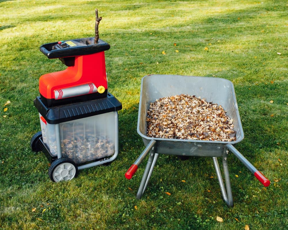 a garden chipper with wood chippings in a steel wheelbarrow