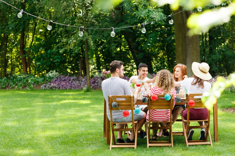 young friends sat on garden furniture and socialising in a garden