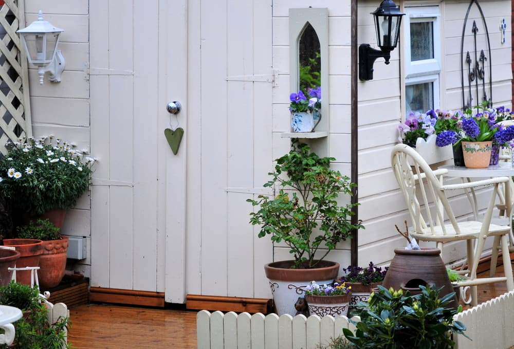 a garden building painted in white with plants growing outside