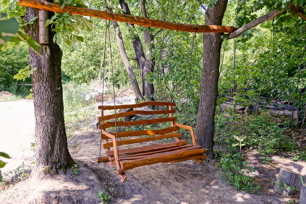 a chair swing made from timber, hanging from two tree trunks