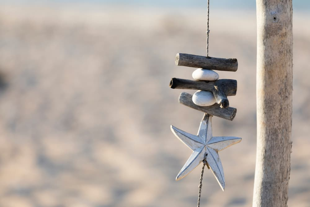a trinket decoration hanging from driftwood at the beach