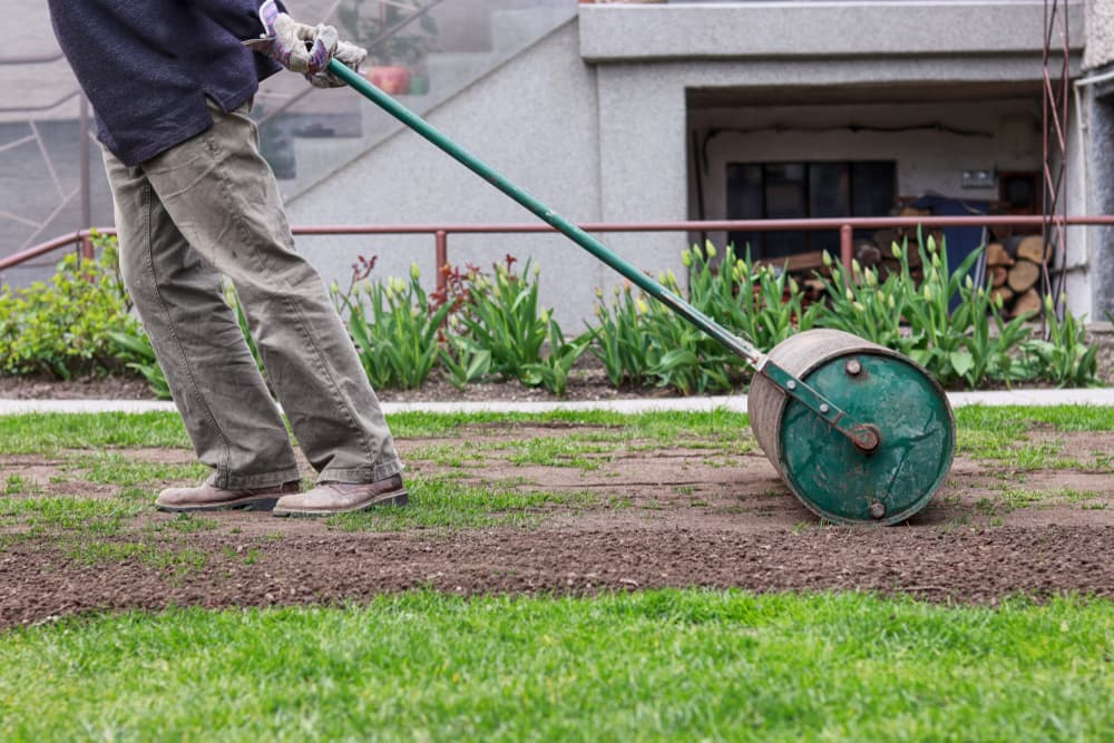 a lawn roller being dragged along a grass surface