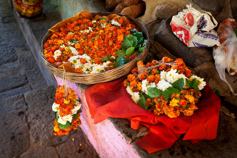a roadside stall in India with tagetes in a large basket