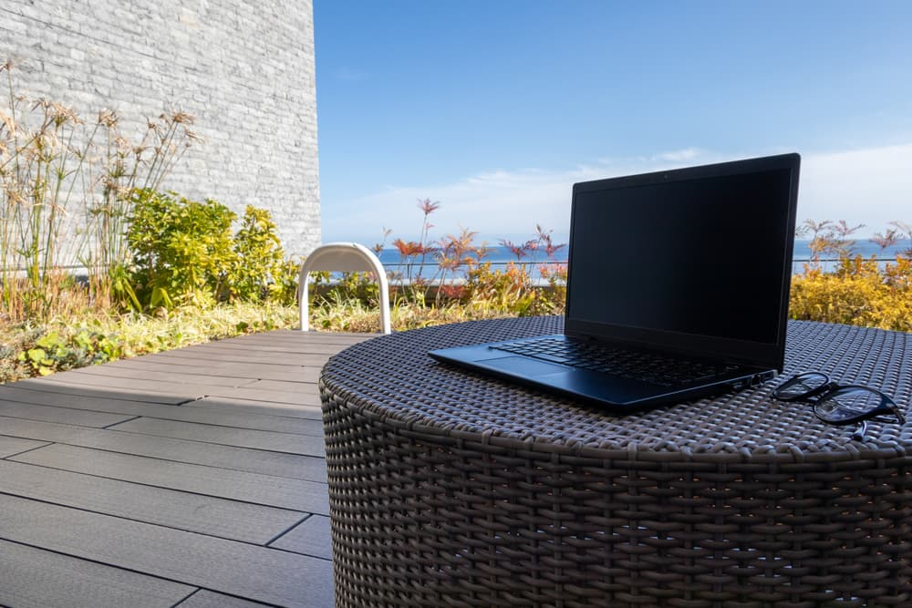 laptop and lgasses sat on a rattan table with decking