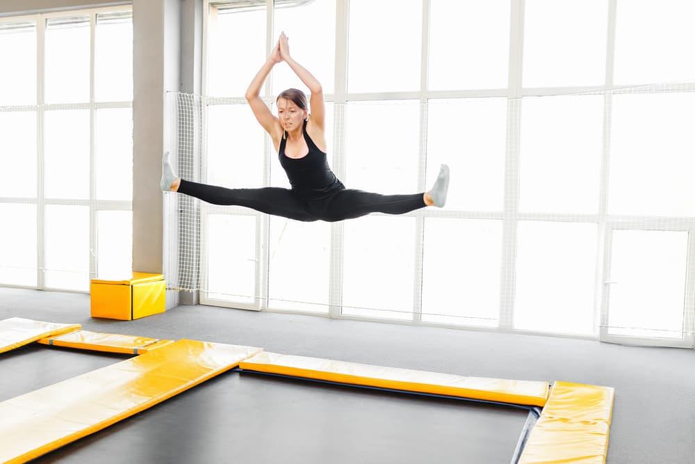 a woman mid-jump on a sunken trampoline