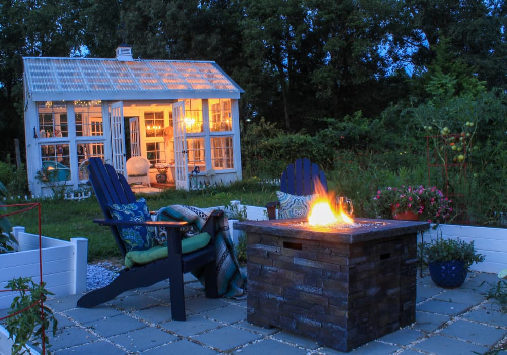 a firepit at nighttime with illuminated garden building in the background