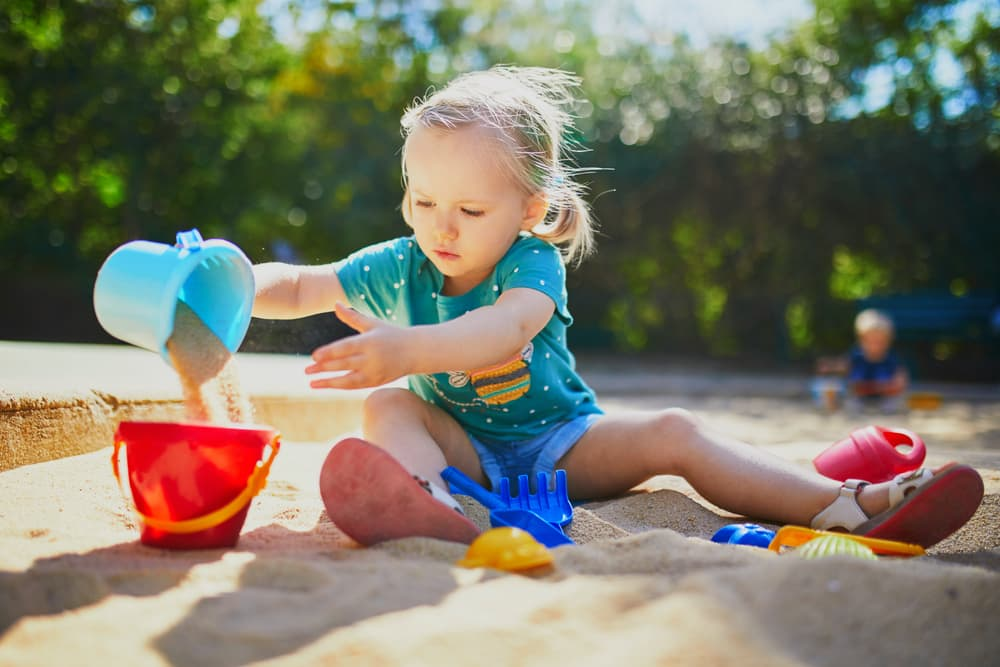 young girl playing in a sandpit