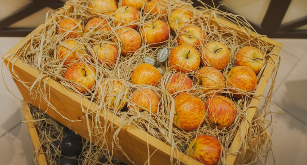striped apples in a wooden box with straw