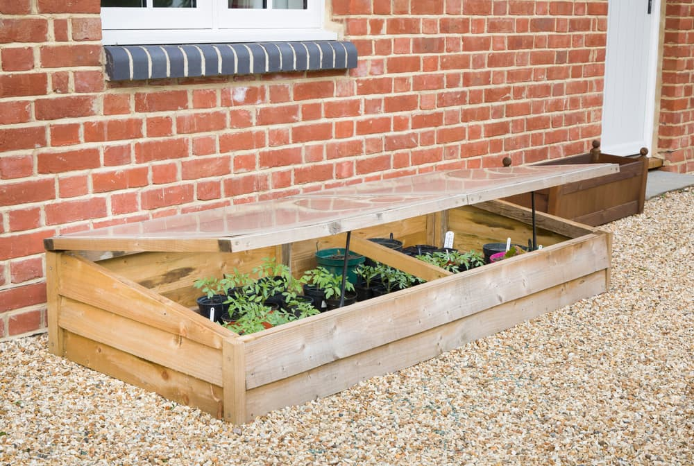 a timber cold frame on a gravel driveway