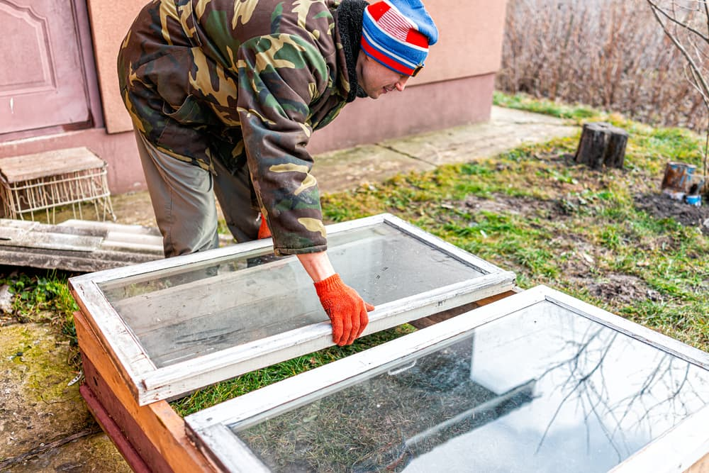 man constructing a cold frame with old materials